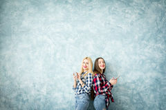 Female friends on the blue wall background Stock Image