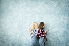 Female friends on the blue wall background Stock Images