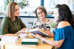 Female friends at book club. Group of women sitting around a table with lots of different books Royalty Free Stock Photo