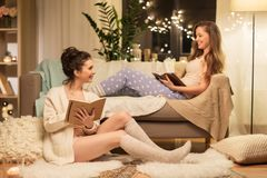Female friends with book and sketchbook at home Royalty Free Stock Photos