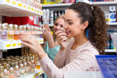 Female friends buying perfume. Cheerful friends buying perfume in fragrance section of supermarket Royalty Free Stock Photography