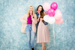 Female friends with candy and baloons Stock Photo