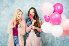 Female friends with candy and baloons Stock Image