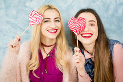 Female friends with candy on the blue background Stock Images