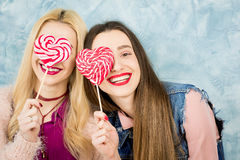 Female friends with candy on the blue background Royalty Free Stock Image