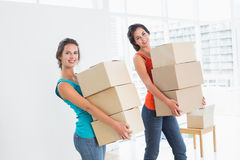 Female friends carrying boxes in in new house Royalty Free Stock Images