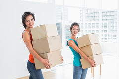 Female friends carrying boxes in in new house Royalty Free Stock Image