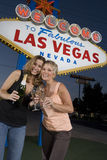 Female Friends With Champagne Against 'Welcome To Las Vegas' Sign Royalty Free Stock Photos