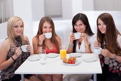 Female friends chatting over coffee. Four stylish attractive young female friends seated at a table chatting over coffee Stock Images