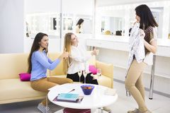 Female friends choosing clothes together in a shop. Drinking chmpagne stock photo