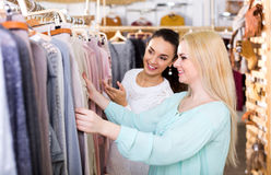 Female friends choosing new tops in shop. Attractive young female friends choosing new tops in shop and smiling Stock Image