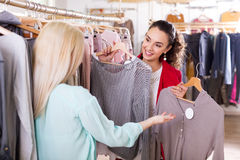 Female friends choosing new tops in shop Stock Photography