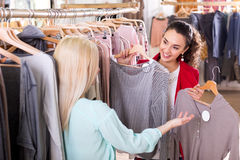 Female friends choosing new tops in shop Stock Images