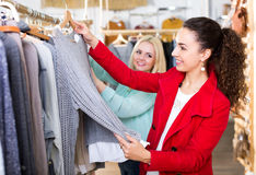 Female friends choosing new tops in shop Royalty Free Stock Photo