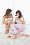 Female friends with coffee cups in bed Royalty Free Stock Photos