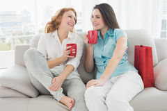 Female friends with coffee cups conversing at home Stock Photos