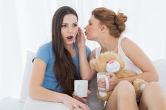 Female friends with coffee cups gossiping in bed Stock Photo