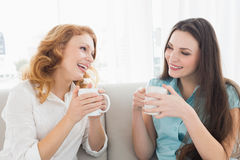 Female friends with coffee enjoying a conversation at home Stock Photography