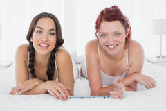 Female friends with digital table lying in bed Stock Images
