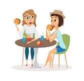Female friends eating. Fast food meal in restaurant. Two people sitting, talking and having lunch burgers, fries and drinking soda. Meeting of young fun and Stock Image