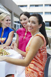 Female Friends Eating Out Together. Group of female friends eating out together at a restaurant Stock Image