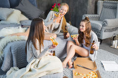 Female friends eating pizza. Three young smiling female friends eating pizza and drinking beer in bedroom Royalty Free Stock Photos