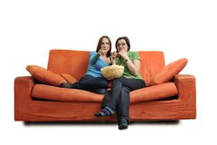 Female friends eating popcorn and watching tv at home Stock Photos
