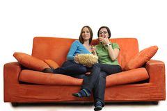 Female friends eating popcorn and watching tv at home Stock Images