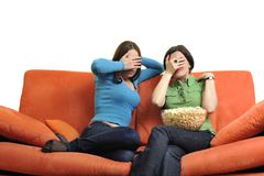 Female friends eating popcorn and watching tv at home Royalty Free Stock Images