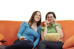 Female friends eating popcorn and watching tv at home Stock Photo