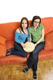 Female friends eating popcorn and watching tv at home Stock Photography