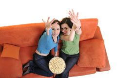 Female friends eating popcorn and watching tv at home Royalty Free Stock Photo