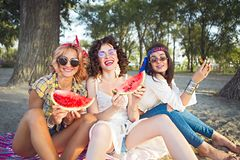 Female friends eating watermelon. On the beach stock photo