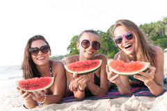 Female friends eating watermelon. Happy smiling female friends eating watermelon on beach Royalty Free Stock Photography