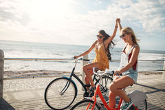 Female friends enjoying cycling on a summer day Royalty Free Stock Images