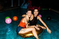 Female friends enjoying evening pool party. Two women in swimming pool with inflatable ring at evening. Female friends enjoying evening pool party Stock Image