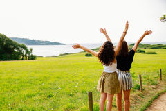 Female friends enjoying the nature. Two female friends with raised arms contemplating the landscape of the countryside and the coast Stock Images