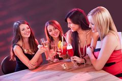 Female friends enjoying a night out. Sitting having cocktails at a table in a nightclub Royalty Free Stock Photo