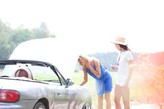Female friends examining broken down car on country road Royalty Free Stock Photo