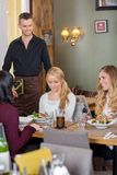 Female Friends With Food On Table While Waiter. Young female friends with food on table while waiter holding menu at cafe Stock Photos