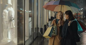 Female Friends in Front of Shop's Show Window. Two female friends are standing in front of the show window of clothing shop and talking. They are holding stock footage