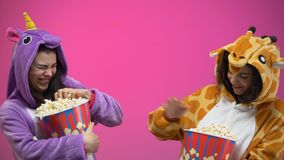 Female friends in funny pajamas having fun, throwing popcorn to each other. Stock footage stock video