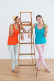 Female friends gesturing thumbs up against ladder in new house Royalty Free Stock Photo