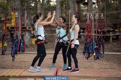 Female friends giving high five to each other after completing zip line. Happy female friends giving high five to each other after completing zip line in park Royalty Free Stock Photos