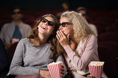 Female friends gossiping while watching movie. In theatre royalty free stock photos