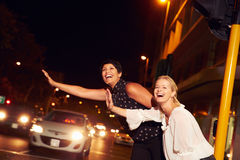 Female friends hailing taxi on city street at night Royalty Free Stock Images