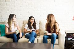 Female friends hanging out. Group of three female friends talking about something serious while drinking some coffee Royalty Free Stock Photography