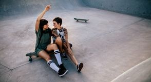 Female friends hanging out at skate park. Two women skateboarders sitting on long board at skate park Stock Photos