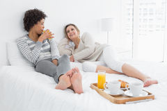 Female friends having breakfast in bed Stock Photos