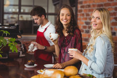 Female friends having coffee at coffee shop Stock Photos